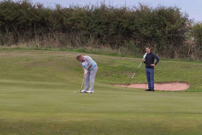 Dave Barnes putting on 17th green watched by his son/ caddy for the day